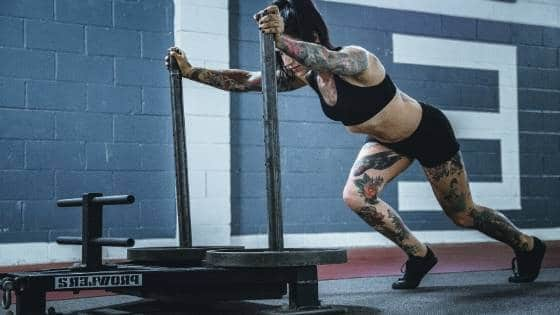 Fit woman pushing a sled.