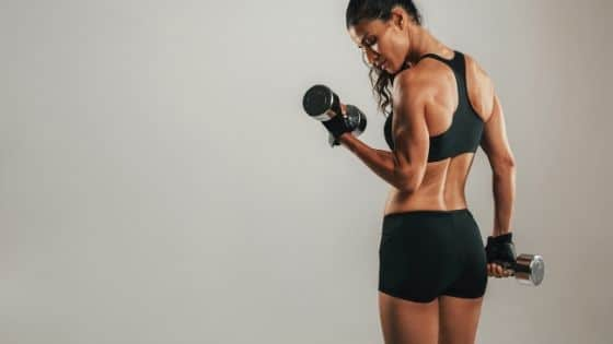 Woman lifting weight to prevent muscle loss during weight loss.