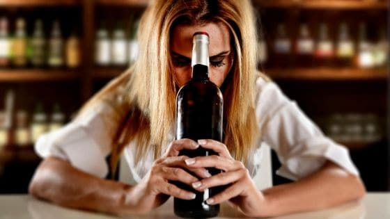 Woman holding a bottle of wine wondering how to naturally detox her body.