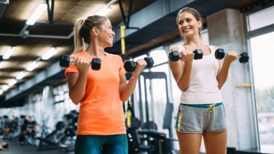 Image of two women exercising at the gym lifting dumbbells.