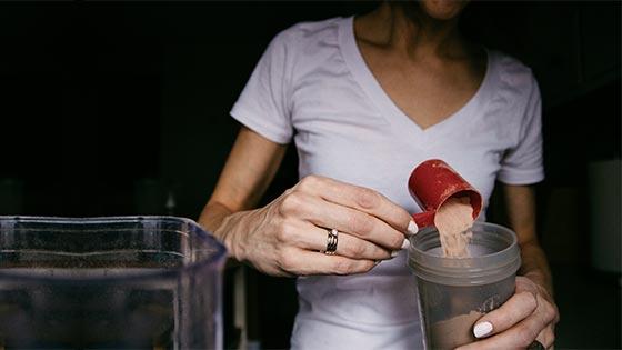 Woman making a keto protein powder shake.